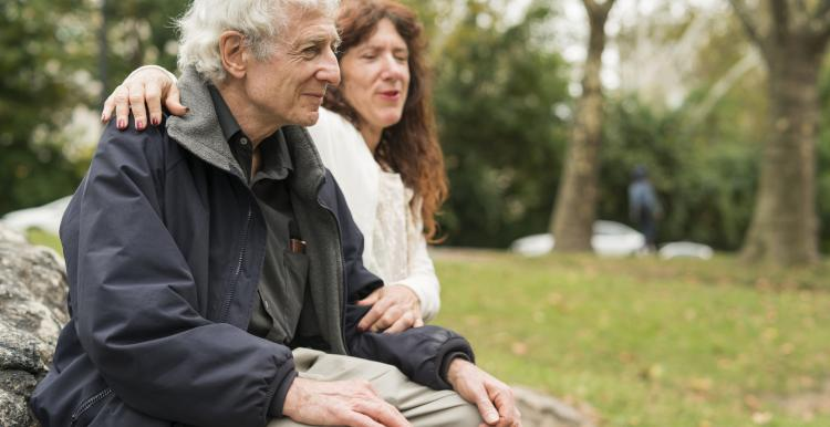 Elderly person sitting on a bench with a friend