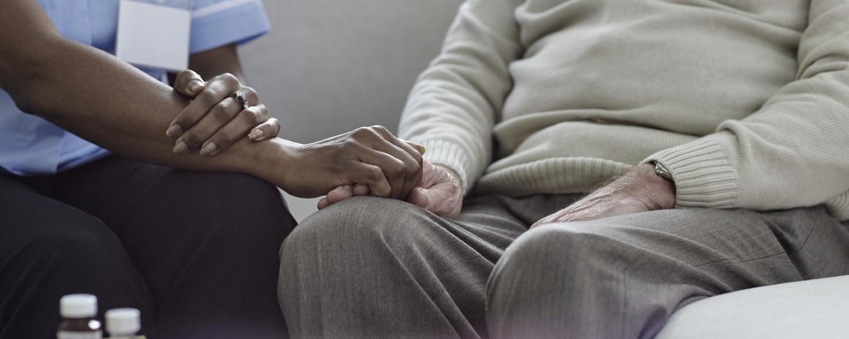 A nurse holding an old man's hand on the sofa