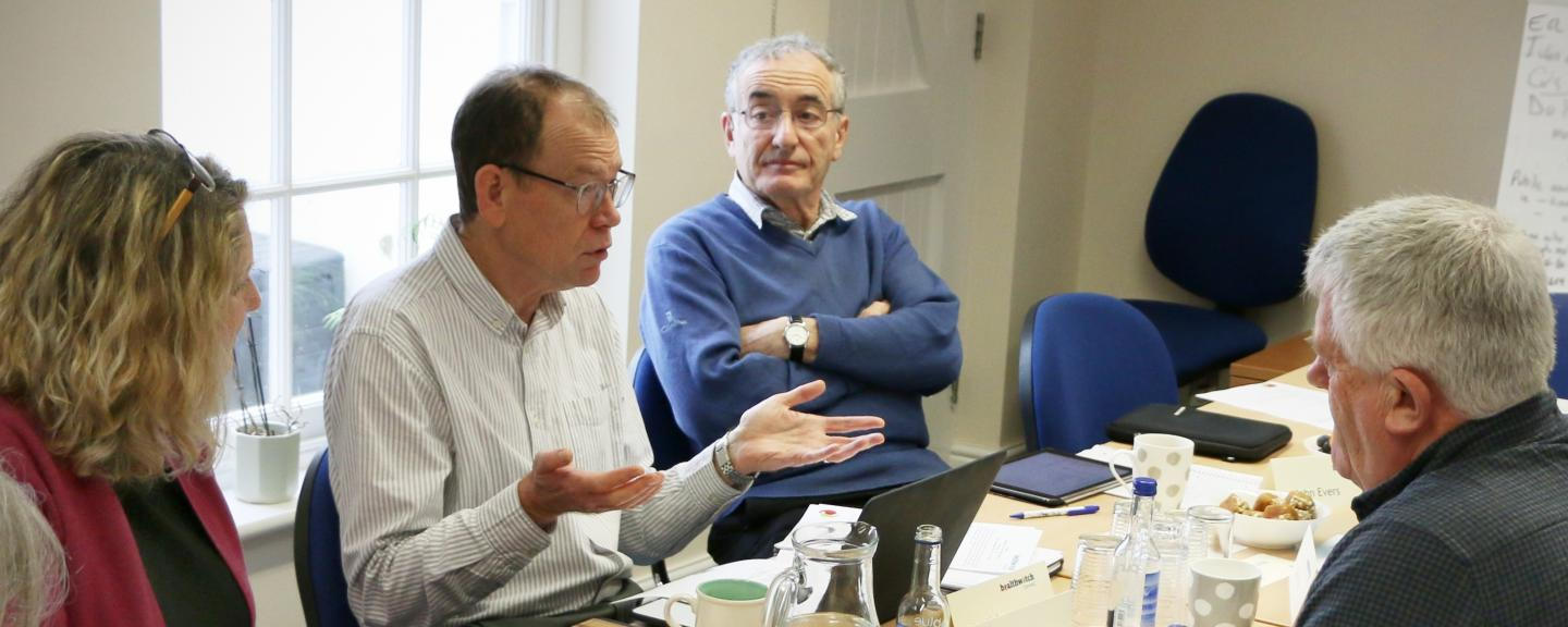 Three people having a discussion at a board meeting