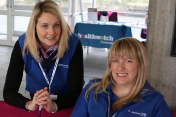Two women from Healthwatch Cornwall smiling at an event