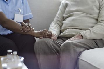 A nurse holding an old man's hand on the sofa