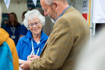 Woman from Healthwatch Cornwall smiling with a man filling in a form