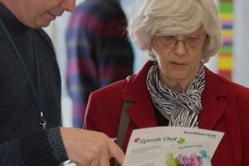 A woman looking at a Healthwatch leaflet while a man points