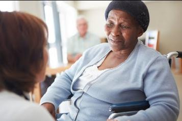 Elderly woman in a nursing home being spoken to by a nurse