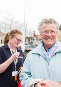 Woman smiling with a Healthwatch employee in the background